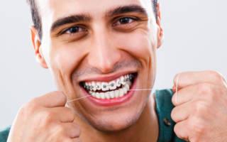 Мужчина чистит зубы нитью