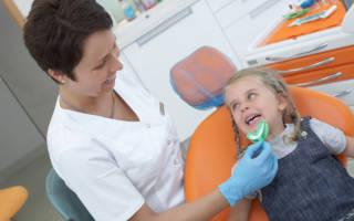 Врач фторирует зубы девочке
