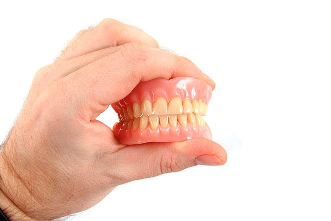 Зубные протезы в руках