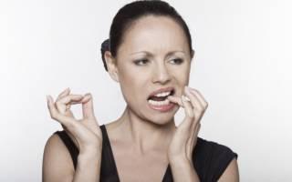 Женщина трогает зубы
