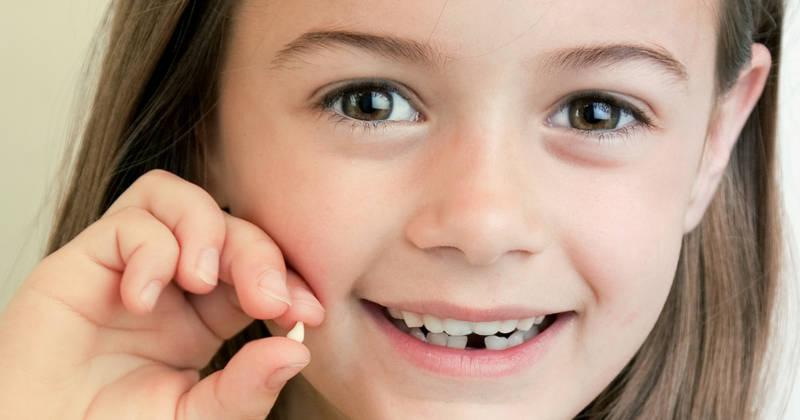 Девочка с молочным зубом в руке
