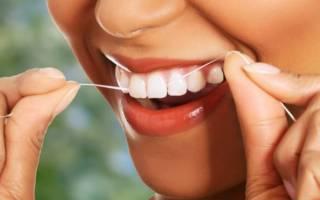 Женщина чистит зубы зубной нитью