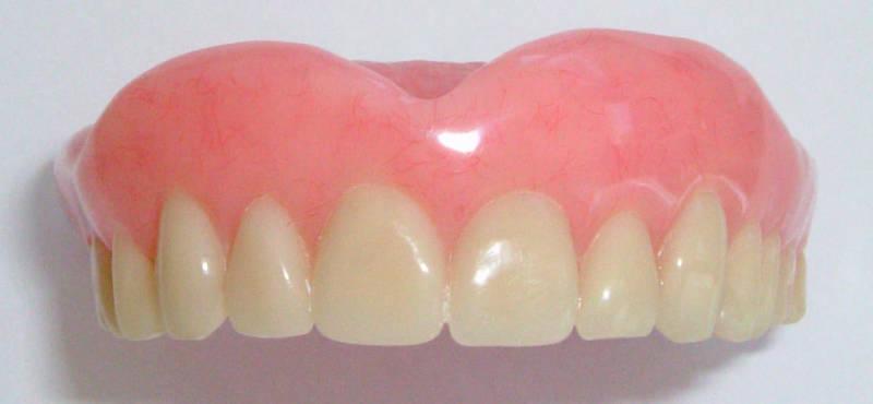 Зубной протез на белом фоне