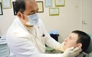 Врач осматривает челюсть пациента