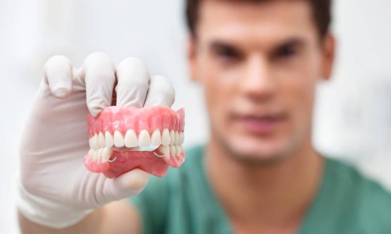 Стоматолог с протезом в руке