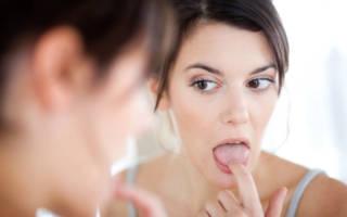 Девушка осматривает язык в зеркало
